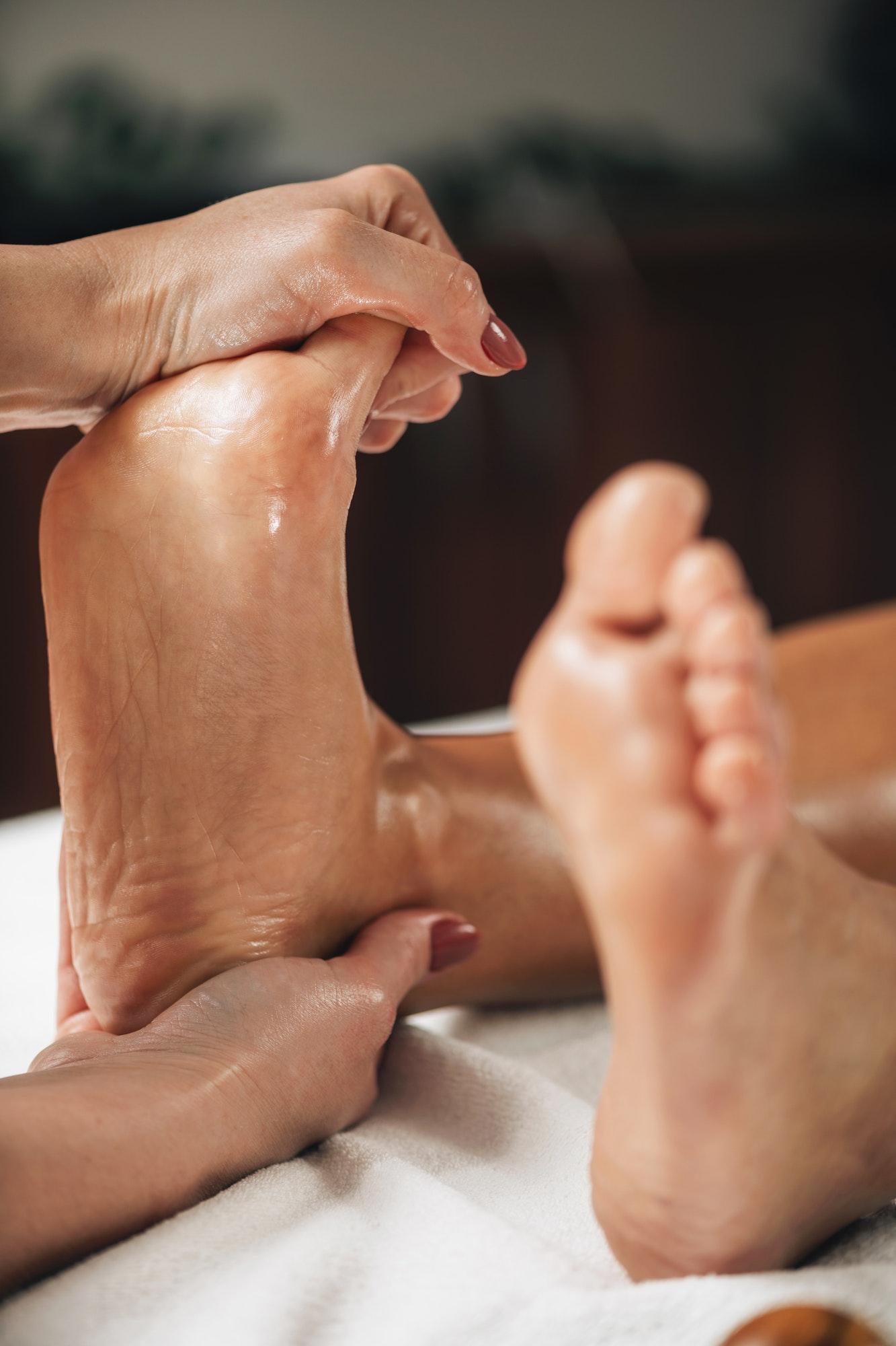 Woman Receiving Foot Massage from Female Masseuse at a Wellness center